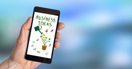 Hand holding a smartphone with business ideas concept