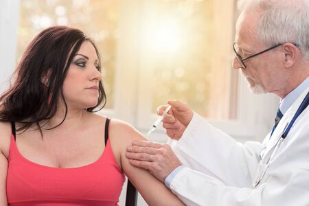 inyeccion intramuscular: Doctor injecting vaccine to attractive young woman, light effect