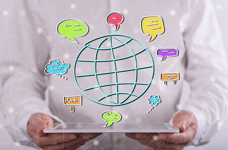 Global communication concept above a tablet held by a man in background Stock Photo