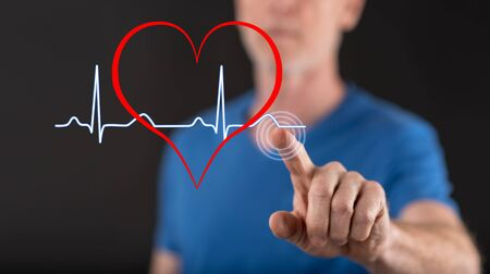 Man touching a heart beats graph on a touch screen with his finger Banco de Imagens - 92345410
