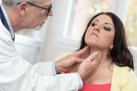 Doctor checking thyroid of a young patient