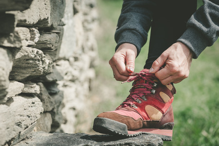 Hands of woman lacing her shoes on a stone during a hike
