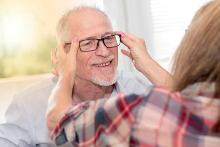 Senior man testing new eyeglasses in optician store, light effect