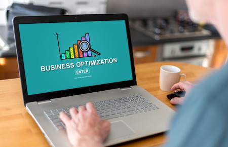 Man using a laptop with business optimization concept on the screen