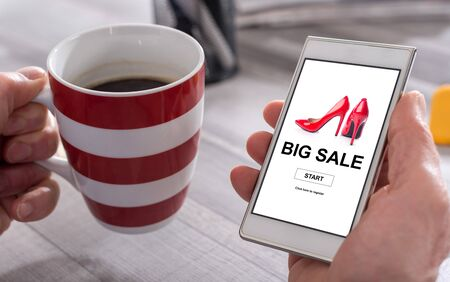 Male hand holding a smartphone with big sale concept