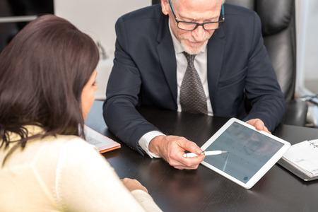 Consultant advising young woman at office Stock Photo