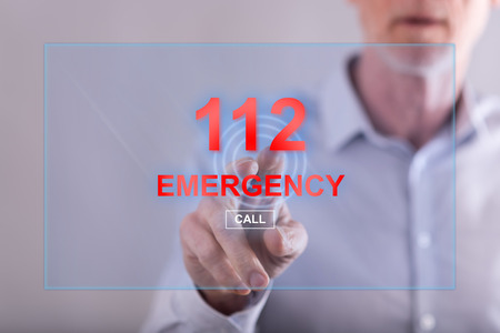 Man touching an emergency concept on a touch screen with his finger