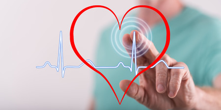 Man touching a heart beats graph on a touch screen with his finger Banco de Imagens - 99295547