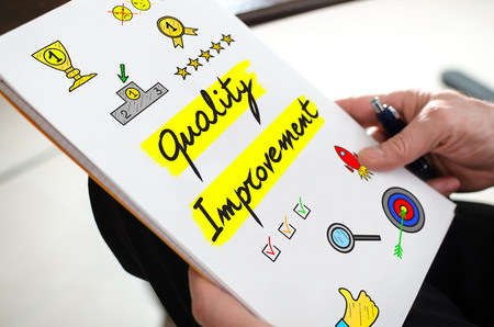 Quality improvement concept on a paper held by a hand
