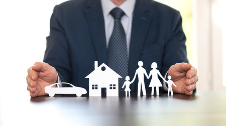 Insurer protecting a family, a house and a car with his hands Stock Photo