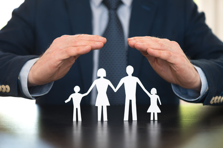 Insurer protecting a family with his hands Stock Photo