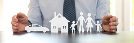 Insurer protecting a family, a house and a car with his hands Stockfoto