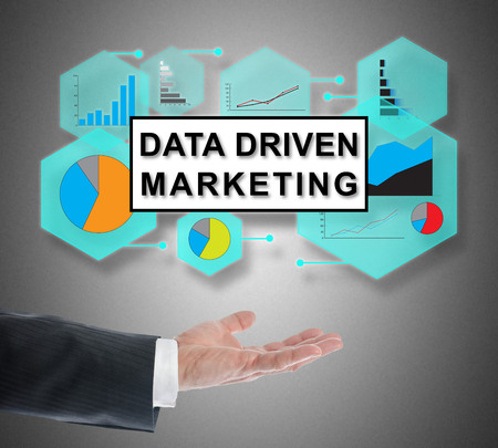 Data driven marketing concept levitating above a hand on grey background Stock Photo