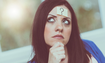 Thinking young woman with question mark on her forehead