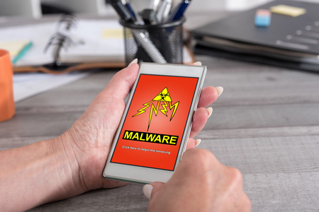 Female hand holding a smartphone with malware concept