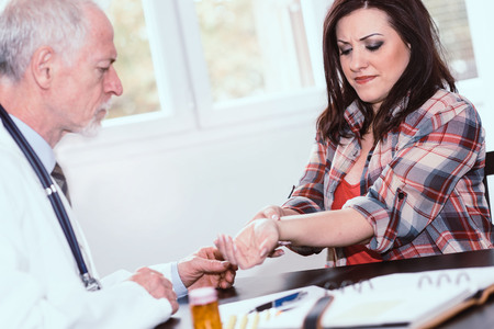Doctor examining wrist of a female patient in medical office