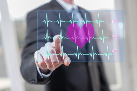 Man touching a heart beats graph concept on a touch screen with his fingers Banco de Imagens