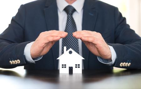 Verzekeraar die een huis met zijn handen beschermt