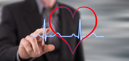 Man touching a heart beats graph on a touch screen with his finger Banco de Imagens - 105211259