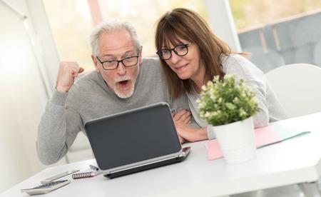 Happy mature couple having an amazing surprise on laptop Banque d'images