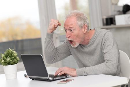 Happy mature man having an amazing surprise on laptop
