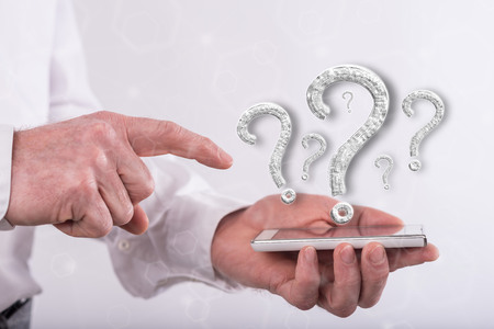 Question concept above a smartphone held by a man Banque d'images