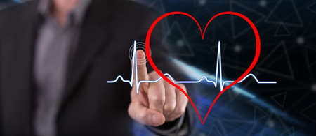 Man touching a heart beats graph on a touch screen with his finger Banco de Imagens - 109335987