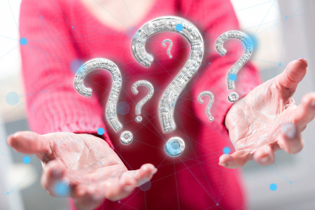 Question concept above the hands of a woman in background Banco de Imagens