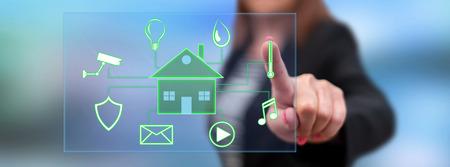 Frau, die mit ihrem Finger ein digitales Smart-Home-Automatisierungskonzept auf einem Touchscreen berührt