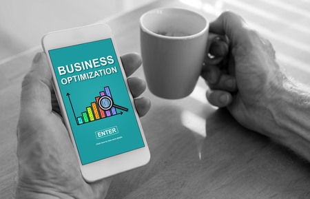 Male hands holding a smartphone with business optimization concept and a cup of coffee Stock Photo