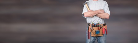 Building worker with crossed arms and tool belt on blurred background