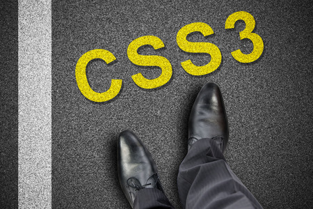 Feet in front of word css3 printed on the road