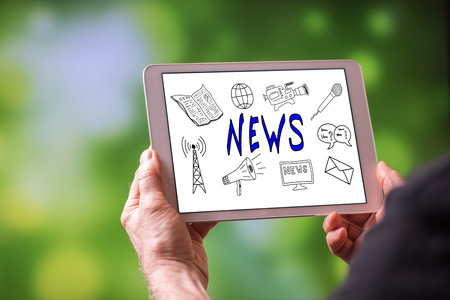 Man holding a tablet showing news concept Imagens