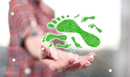 Carbon footprint concept above the hand of a woman in background