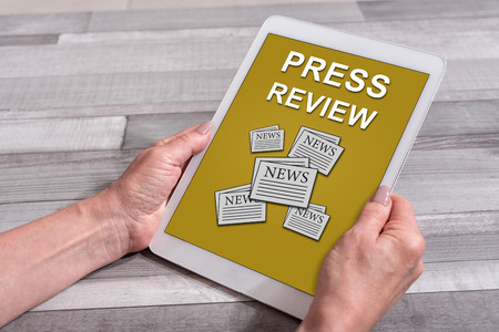 Mani femminili che tengono un tablet con il concetto di rassegna stampa