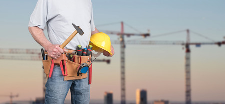 Building worker with tool belt and helmet on a construction site background Stockfoto