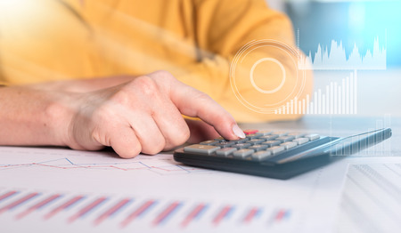 Hands of a female accountant working on financial documents and using a calculator