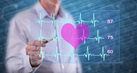 Man touching a heart beats graph concept on a touch screen with a pen