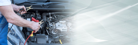 Car mechanic using cables to start a car engine. panoramic banner