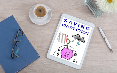 Top view of a desk with saving protection concept on a digital tablet Reklamní fotografie
