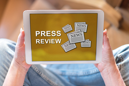 Tablet screen displaying a press review concept Archivio Fotografico - 115952373