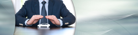 Insurer protecting a car with his hands. panoramic banner Stock Photo