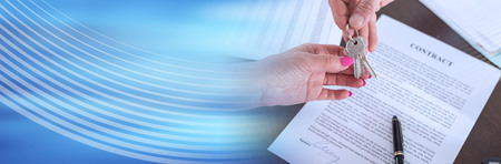 Realtor giving house keys to his client after signing the contract (random english dummy text used). panoramic banner Stock Photo