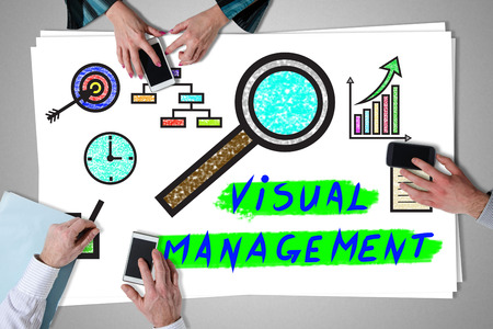 Visual management concept placed on a desk with hands using smartphones Stock Photo