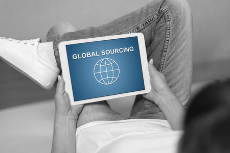 Woman looking at global sourcing concept on a tablet