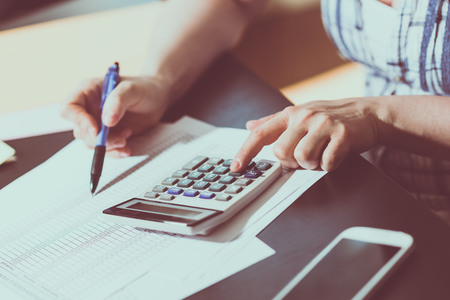 Female accountant using calculator in office Foto de archivo