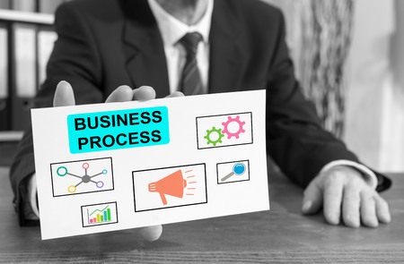 Businessman showing an index card with business process concept Stockfoto
