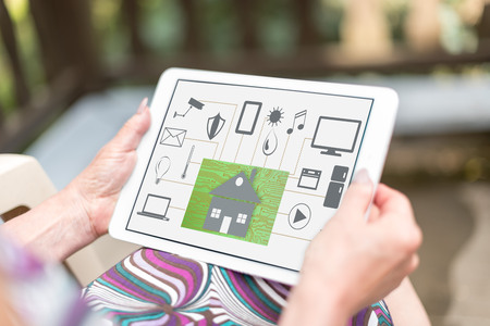 Home automation concept shown on a tablet held by a woman