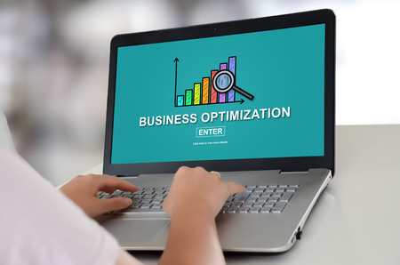Woman using a laptop with business optimization concept on the screen Stock Photo