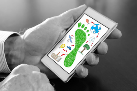 Hand holding a smartphone with carbon footprint concept